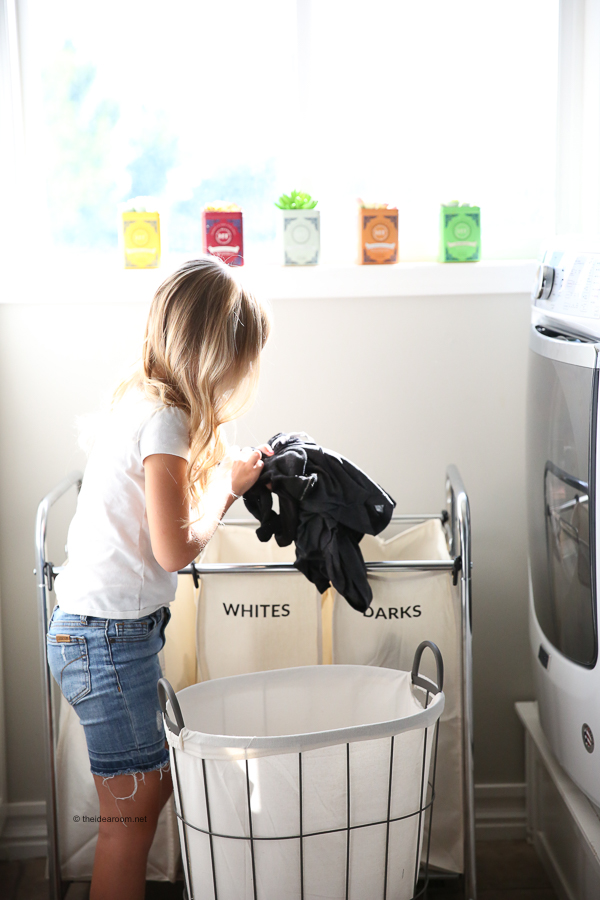 Girl separating laundry in to colors and whites